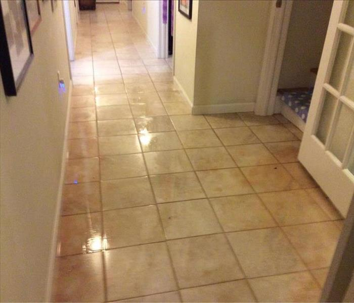 The tile flooring of the hallway is covered by at least 1/2 inch of water