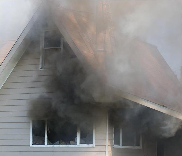 black smoke coming out of windows from a burning house