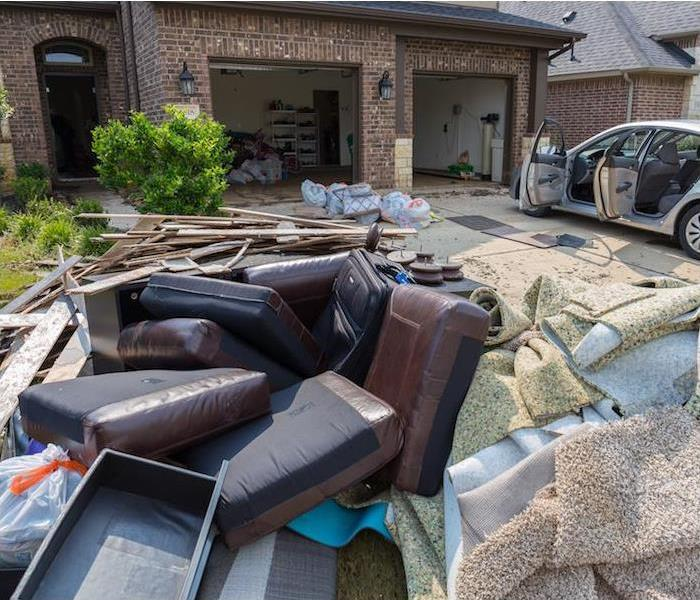 water damaged furniture, home items and ripped up carpet sitting on driveway of brick home
