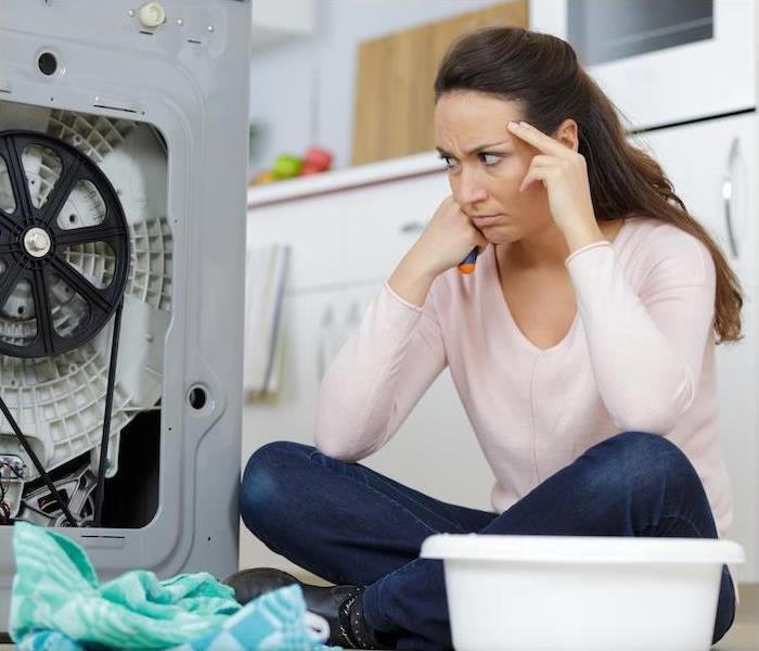 frustrated woman on floor looking at broken washer