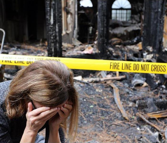 """woman with hands covering face upset with burnt house in background """