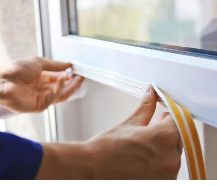 a person placing weather stripping on a white window